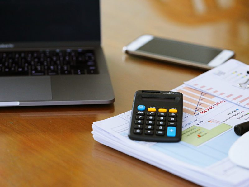 Computer on table with smartphone, documents and calculator closeup blur background