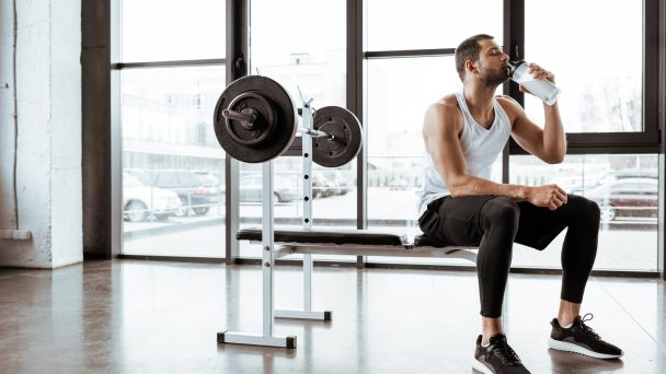 handsome sportsman drinking protein milkshake near barbell in gym