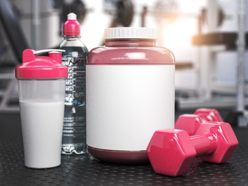 Pink whey protein can with pink dumbbell sand shaker on the floor of gym. Mock up.