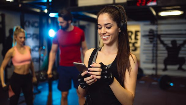 Portrait of young sportswoman with smartphone listening to music in gym.