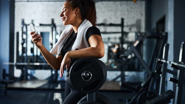 Smiling female sport instructor with smartphone in gym